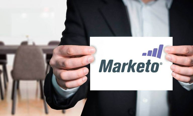 man holding a piece of paper which has Marketo logo on it