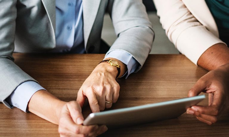 close up on two hands holding a tablet in an office setting