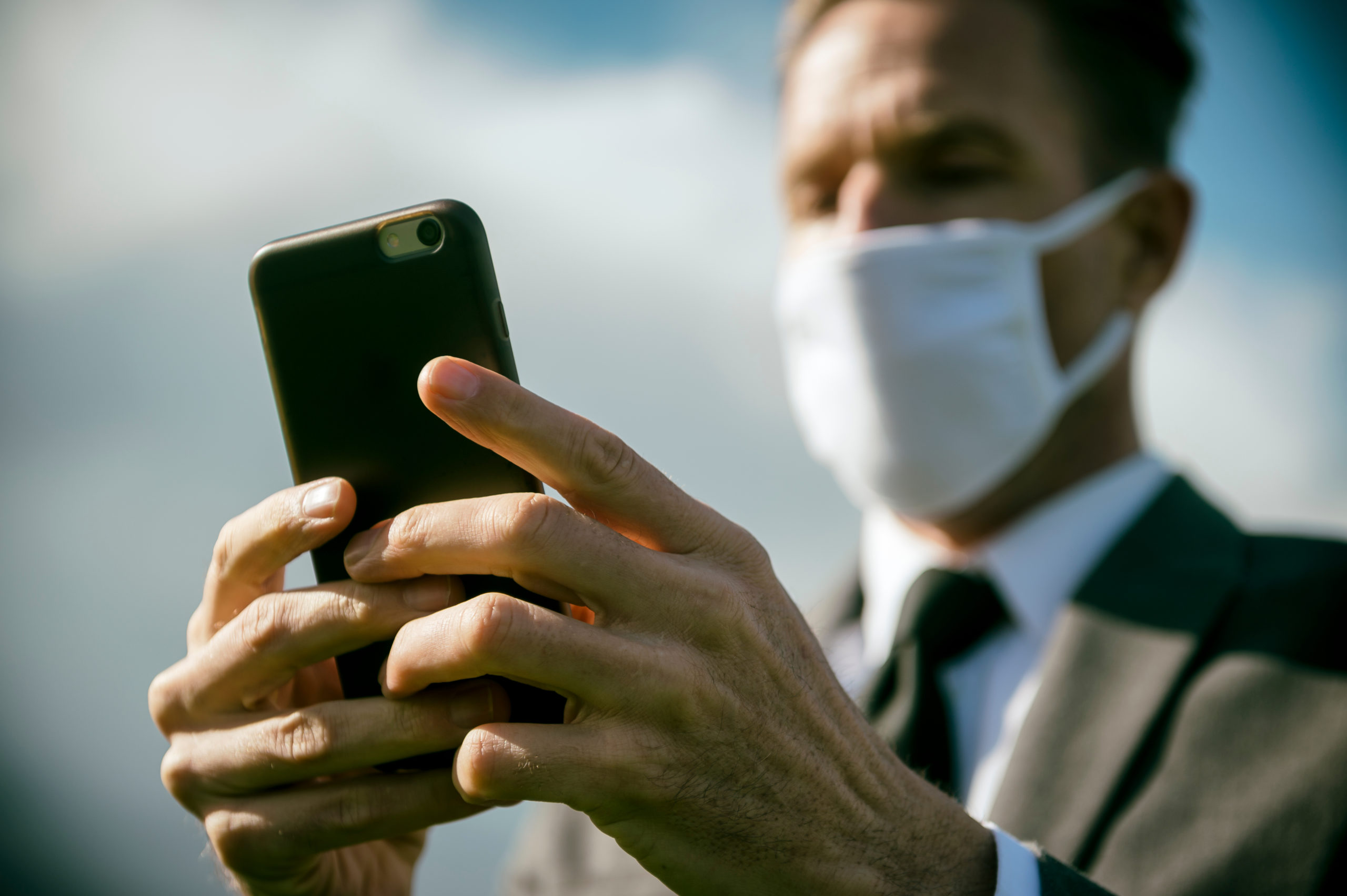 Man with a mask checking his phone